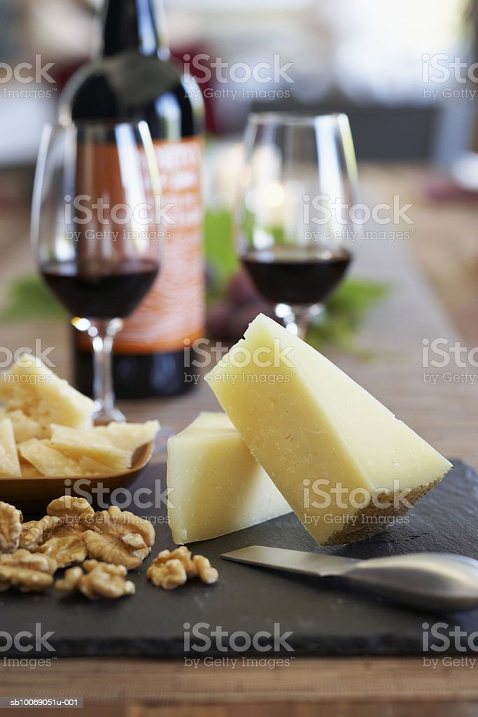 Cheese and nuts on cutting board, wine glasses in background, close-up royalty free stockfoto