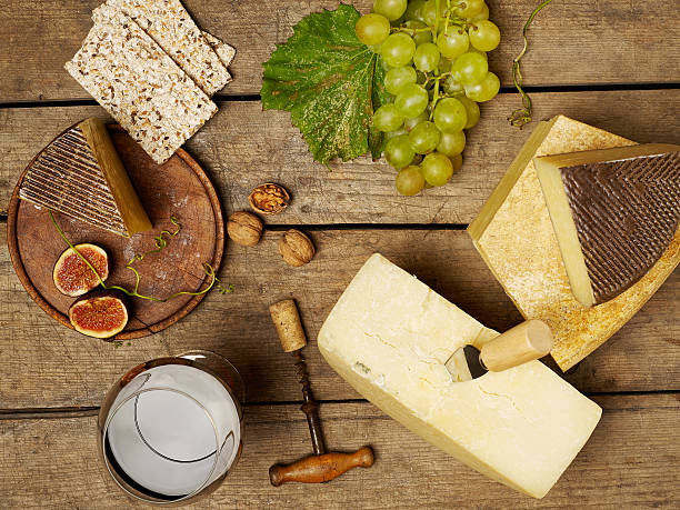 Cheese and wine on wooden table stock photo