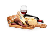 Wooden cutting board with a selection of cheeses, spanish chorizo, a glass of red wine and bread isolated on white background. A red wine bottle is laying behind the cutting board. Predominant color is yellow. High key DSRL studio photo taken with Canon EOS 5D Mk II and Canon EF 100mm f/2.8L Macro IS USM.