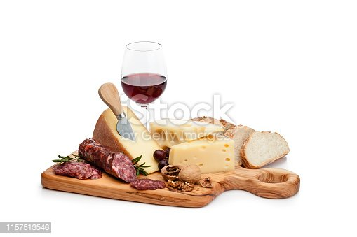 Cheese and wine: cutting board with cheese slices, spanish chorizo, grape and walnuts isolated on white background. A red wine bottle and a wineglass are behind the cheese tray. Useful copy space available for text and/or logo. High key DSRL studio photo taken with Canon EOS 5D Mk II and Canon EF 100mm f/2.8L Macro IS USM.