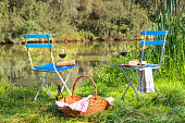 Cheese and wineglasses on Two folding chairs with picnic basket for breakfast outdoors at lake