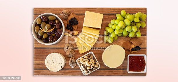 Delicious Cheese Assortment on a wooden board with fruit, nuts, jelly, and olives. Gourmet Charcuterie Arrangment.