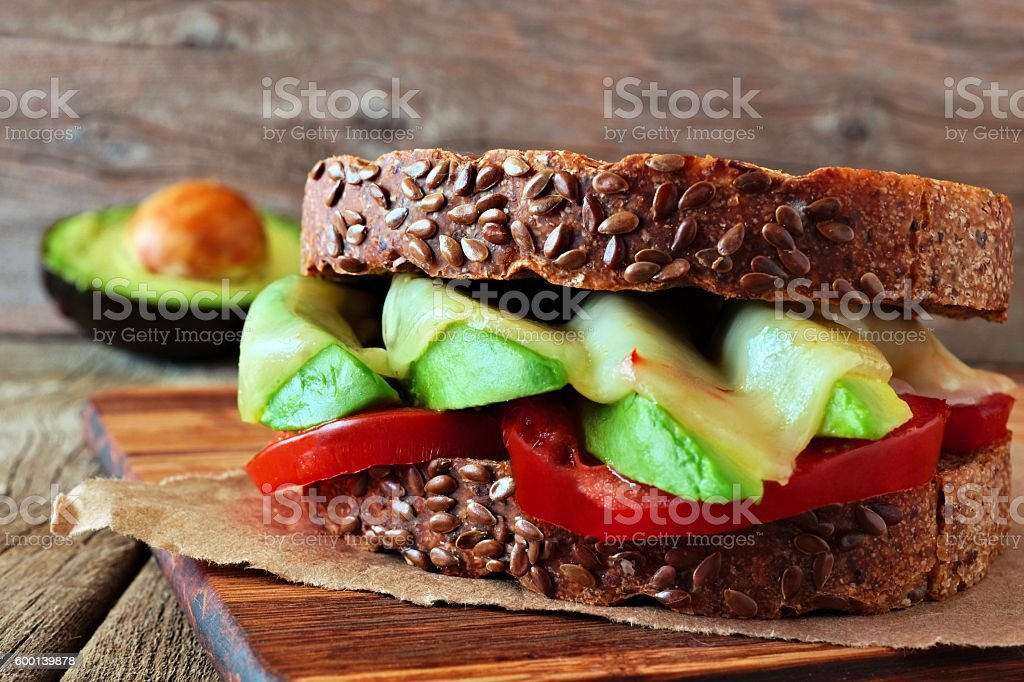 Cheese, avocado, tomato sandwich on whole grain bread against wood stock photo