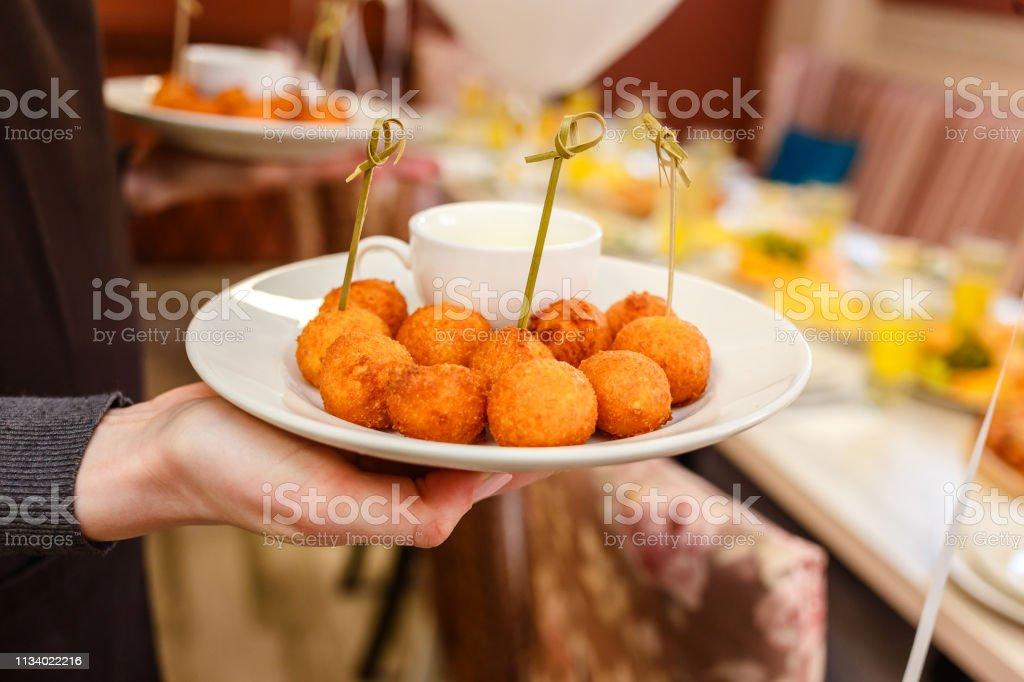 bolas de queijo nas mãos do garçom - foto de acervo
