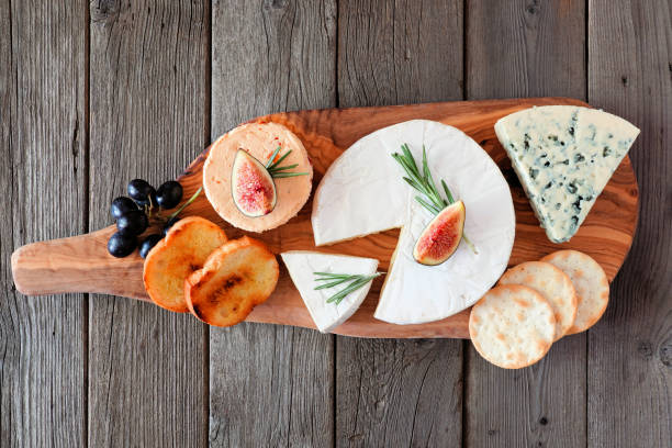Cheese board with a selection of cheeses, crackers, figs and grapes, above view on wooden serving board stock photo
