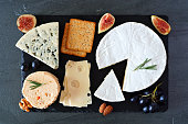 istock Cheese board with a selection of cheeses, crackers, figs and nuts, above view on a slate serving board 1180273801