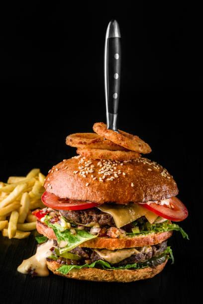 käse-burger mit gegrilltem fleisch, käse, tomaten und zwiebelringe auf dunklen holzoberfläche. ideal für werbung. close-up - mittagspause schild stock-fotos und bilder