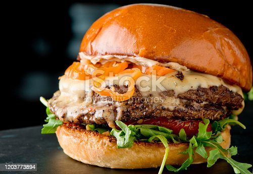 Cheese Burger. Classic American favorite cuisine. Hamburger with fried onions, grilled mushrooms and melted cheeses and served with hand cut potato chips.