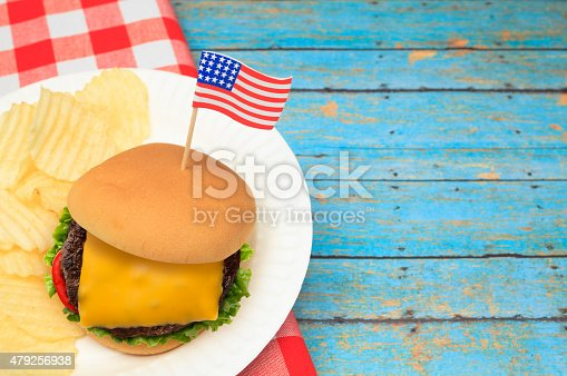 531564432 istock photo Cheese Burger with Patriotic US Flag on Blue Picnic Table 479256938