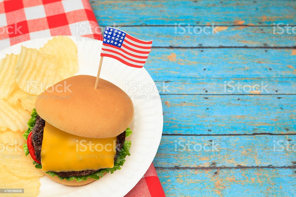Cheese Burger with Patriotic US Flag on Blue Picnic Table stock photo