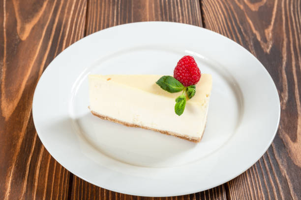 Cheese cake with mint leaves and strawberry on white plate