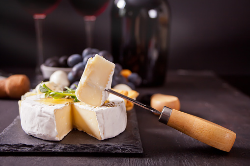 Cheese camembert brie on the board, two glasses and bottle of red wine.