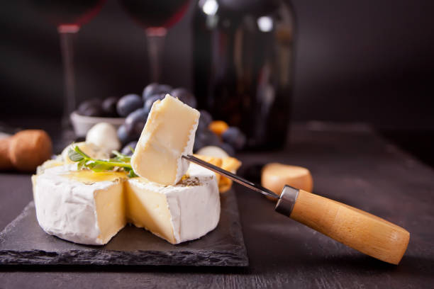 Cheese camembert brie on the board, two glasses and bottle of red wine Cheese camembert brie on the board, two glasses and bottle of red wine. Camembert cheese stock pictures, royalty-free photos & images