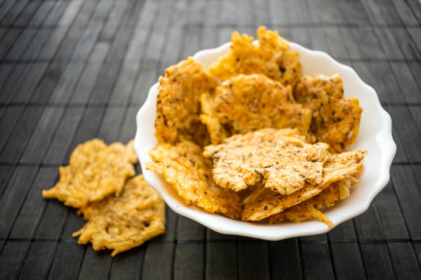 cheese chips snack in a round white bowl on a black wooden background. grain free dippable crispy cheddar cheese chips, keto & low carb. crunchy chip to snack from cheddar, parmesan, asiago, herbs, spices - chipsy zdjęcia i obrazy z banku zdjęć