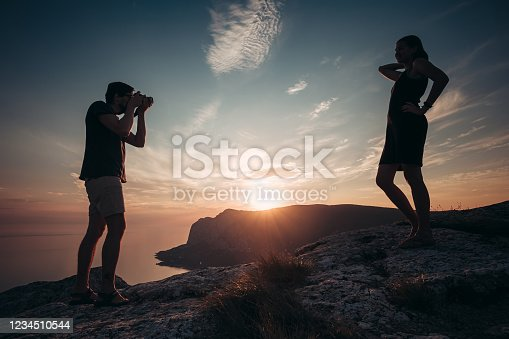 Cheese. Concentrated man taking photo of his girlfriend during picnic. One more shot. Travel together with darling. Couple in love hiking mountains. Summer vacation concept.