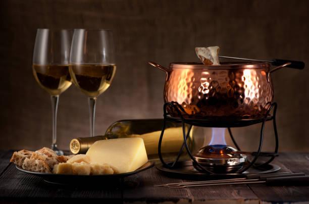 käse-fondue auf rustikalen hintergrund - fondue zutaten stock-fotos und bilder