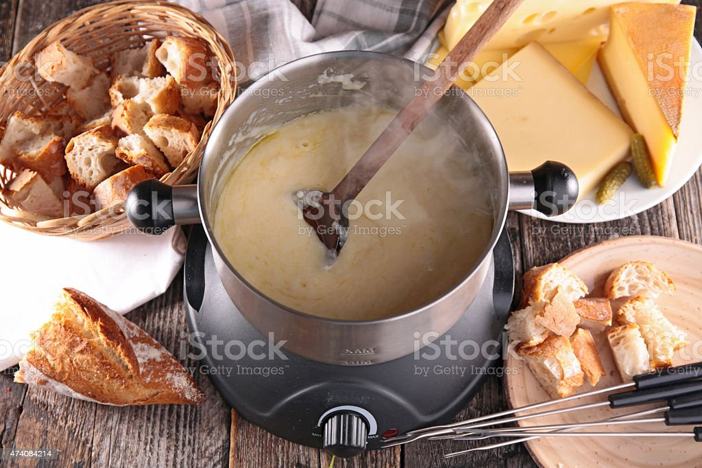 Cheese fondue surrounded by a basket of bread stock photo