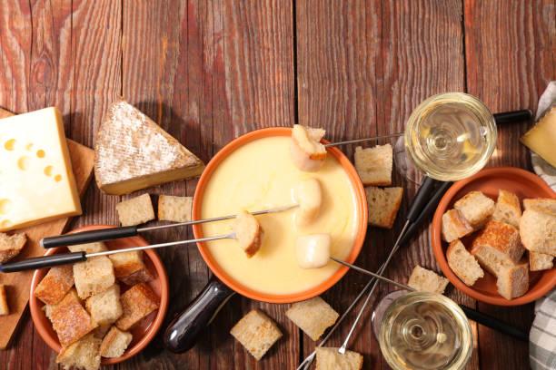 käsefondue mit wein und brot - traditionelles französisches gericht - fondue stock-fotos und bilder