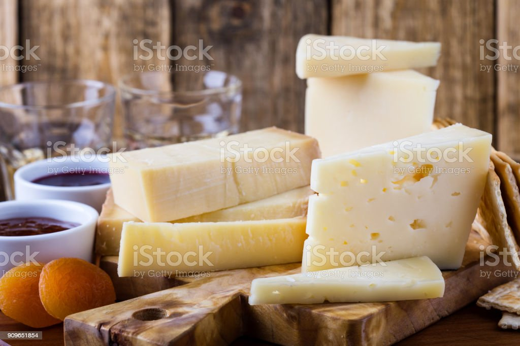 Cheese, fruit jam, nuts and wine on wooden board - foto stock