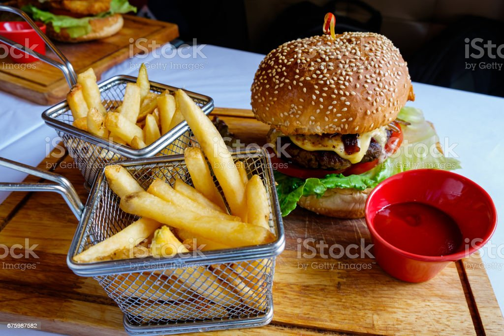Cheese hamburger with fries and ketchup on wooden board – Foto