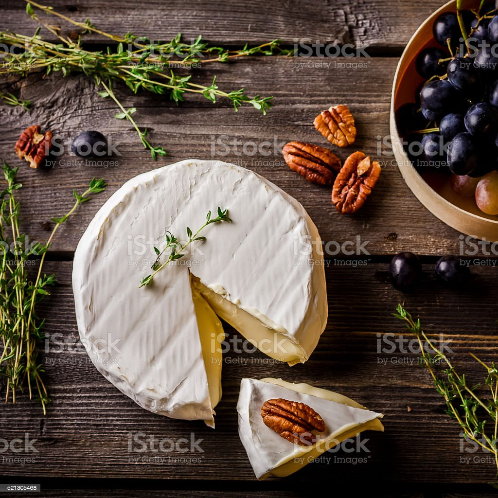 Cheese, herbs, nuts and grape on dark wooden table. stock photo