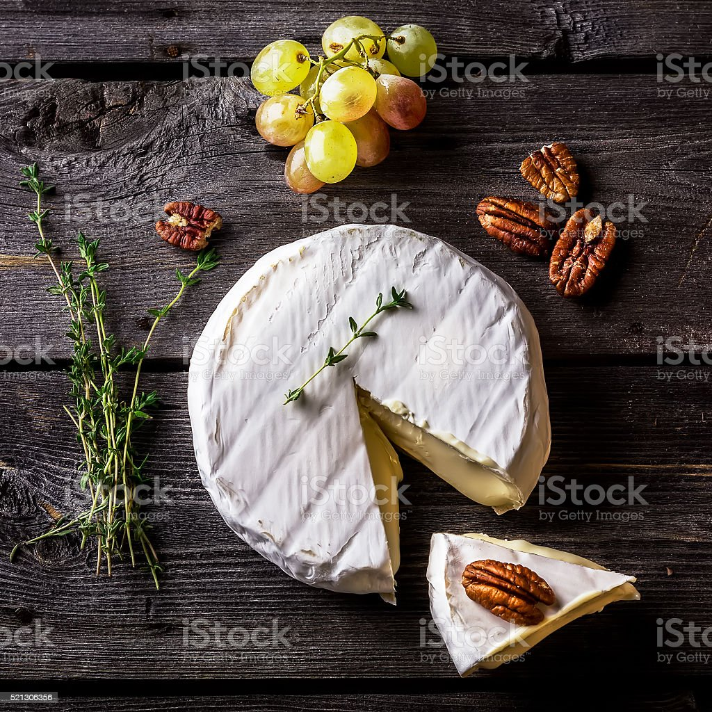 Cheese, herbs, nuts and green grape on dark wooden table. stock photo