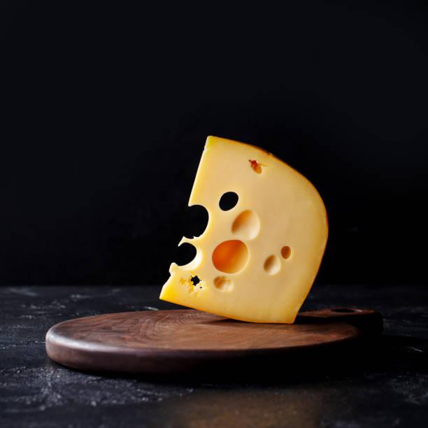 cheese maasdam piece on a cutting board. black stone background. copy space. - maasdam foto e immagini stock