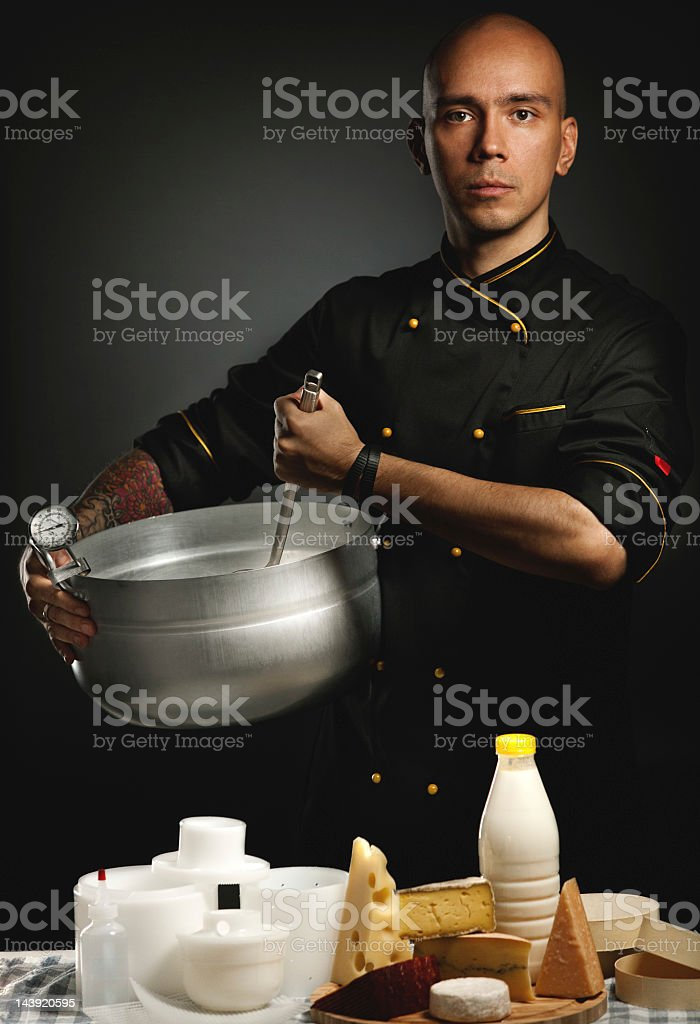 Cheese maker in black chef coat holding a silver pan. stock photo