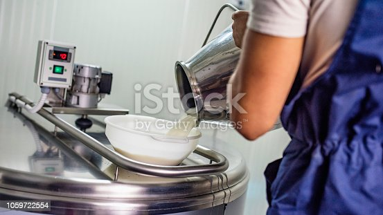 Close-up of a man pouring milk from a jug into a stainless steel heater.