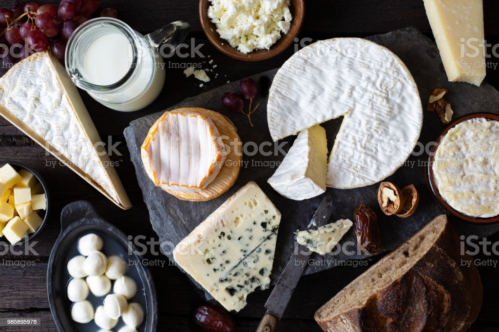 Cheese, milk and dairy products on rustic dark wood and slate...