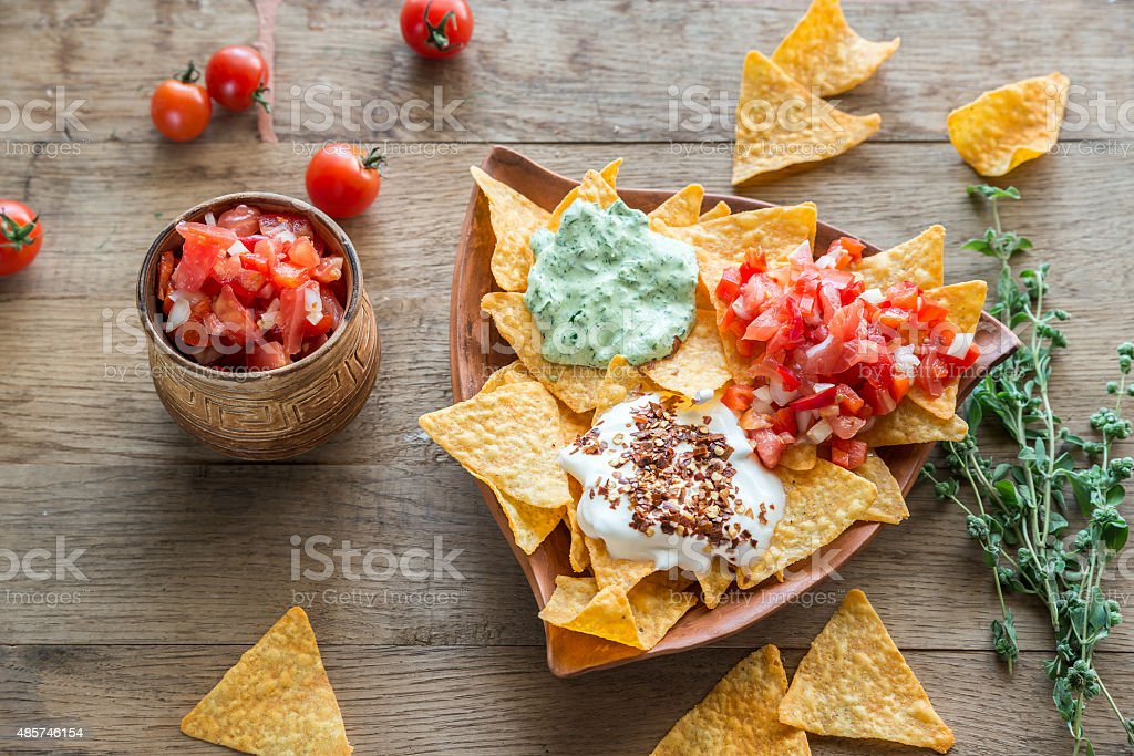 Cheese nachos with different types of sauce stock photo