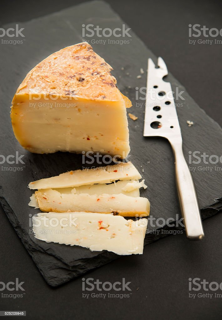 cheese on black slate platter and knife stock photo