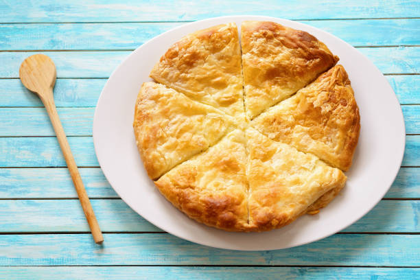 Cheese pie on a blue washed table stock photo