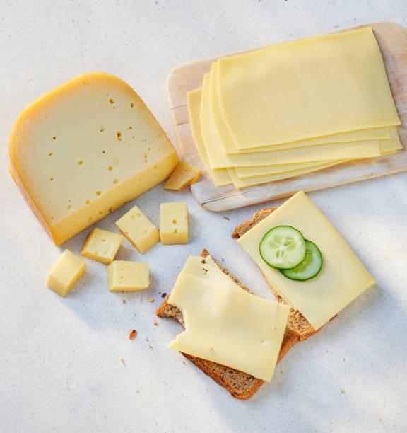 Käse-Stücke und Scheiben auf einer Scheibe Brot – Foto