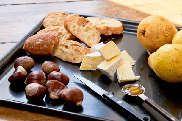 käseplatte: brie, birnen, walnüsse, honig, baguette brot - portugiesische desserts stock-fotos und bilder