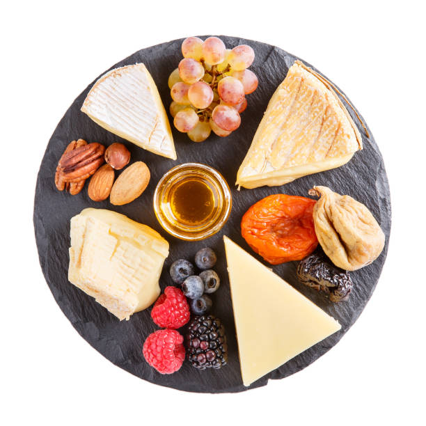 cheese plate. french cheese with nuts, grape, berries, dried fruits and honey on slate board isolated on white. camembert, livarote, pont-l'eveque cheese from normandy and comte cheese. top view. - ser comte zdjęcia i obrazy z banku zdjęć
