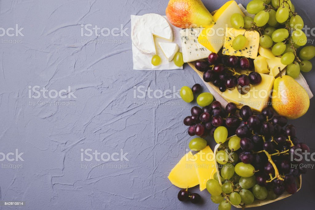Cheese plate served with fresh grapes and pears stock photo