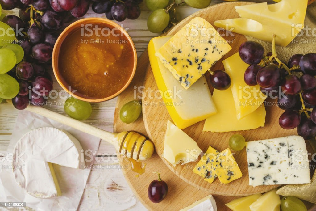 Cheese plate served with honey, fresh grapes and pears stock photo