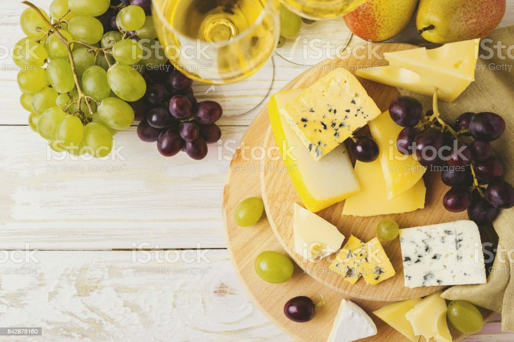 Cheese plate served with wine, fresh grapes and pears stock photo