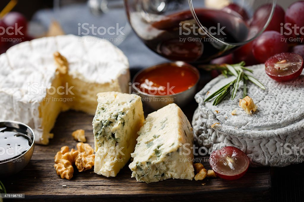 Cheese plate served with wine, jam and honey stock photo
