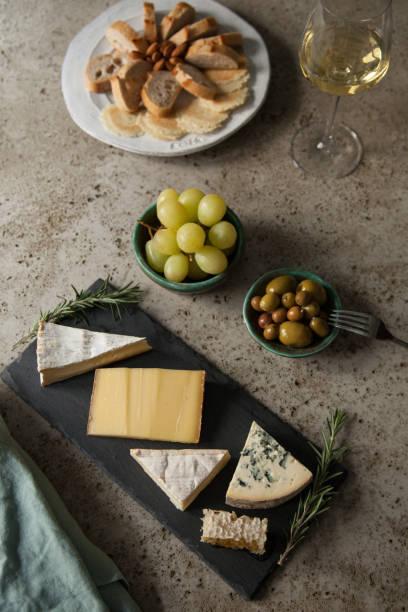 cheese plate with brie, comté, l'évêque, and fourme by ambert - ser comte zdjęcia i obrazy z banku zdjęć
