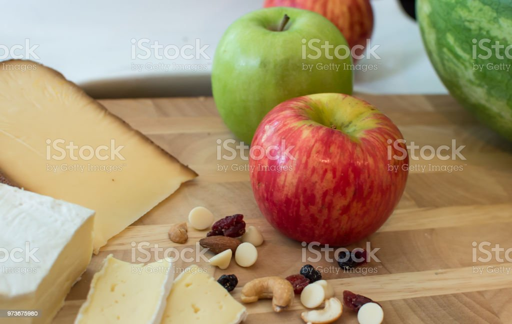 Cheese plate with red apple and green apples still life photography healthy nuts and berry snac stock photo