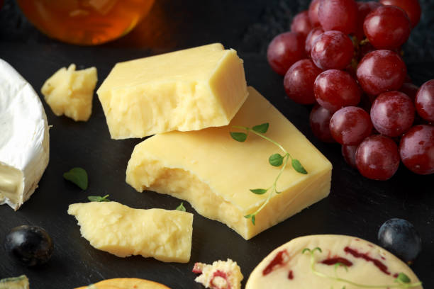 Cheese platter served with grapes, ale chutney, honey, crackers on stone board. Brie, cheddar, red leicester, wensleydale cranberries, blue stilton. Cheese platter served with grapes, ale chutney, honey, crackers on stone board. Brie, cheddar, red leicester, wensleydale cranberries, blue stilton cheddar cheese stock pictures, royalty-free photos & images