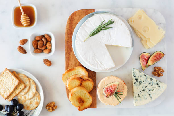 Cheese platter with a selection a cheeses, crackers, figs, nuts and honey, overhead table scene on a marble background stock photo