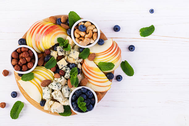Cheese platter with assorted cheeses, blueberry, apples, nuts on white table. Italian cheese  platter and fruit. Top view, overhead stock photo