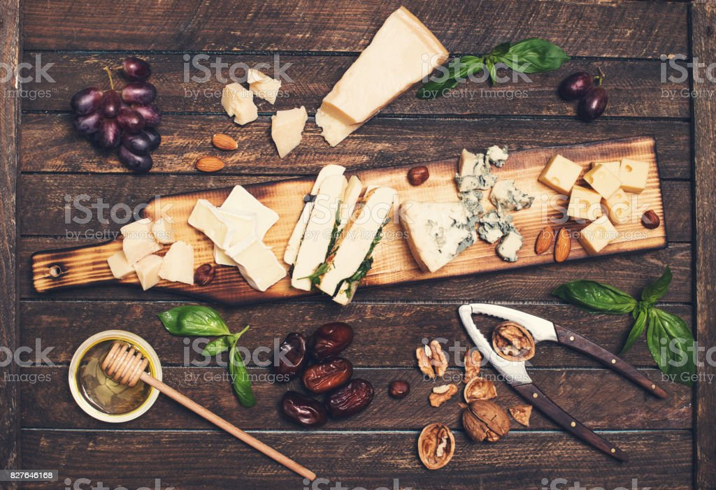 Cheese platter with different cheeses, grapes, nuts, honey and dates on rustic wooden background. Retro styled cheese variety selection on wood board. stock photo