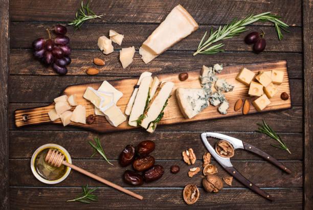 Käseplatte mit verschiedenen Käsesorten, Trauben, Nüssen, Honig, Brot und Termine auf rustikalen hölzernen Hintergrund. Retro-Stil verschiedene Käseauswahl auf dunkle Holzplatte. – Foto