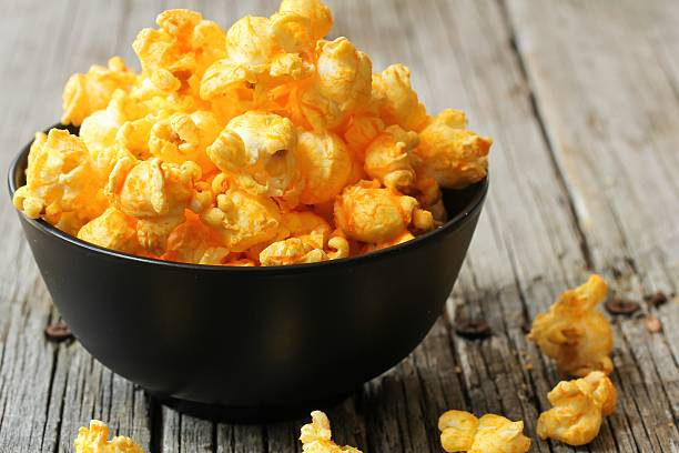 Cheese popcorn in a black bowl, selective focus stock photo