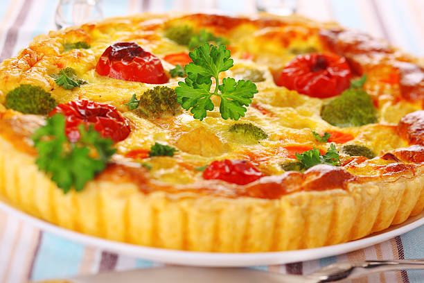 cheese quiche with broccoli, cauliflower, carrots and tomatoes stock photo