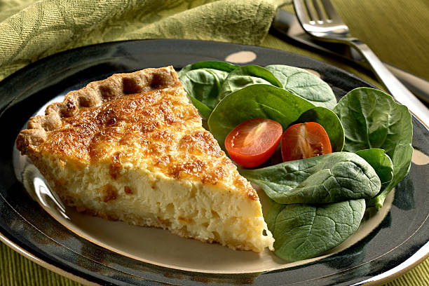 Cheese Quiche with spinach salad Single slice of three cheese quiche on a plate with spinach and tomato salad. Nikon  D3X burwellphotography stock pictures, royalty-free photos & images